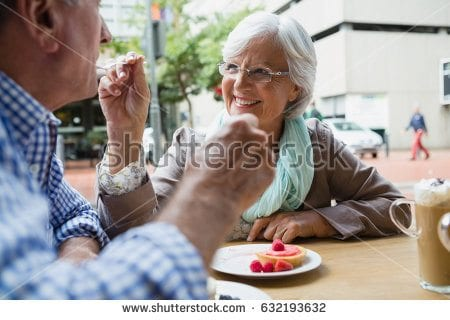 Stock Photo Senior Woman Feeding Sweet Food To Man In Outdoor Caf